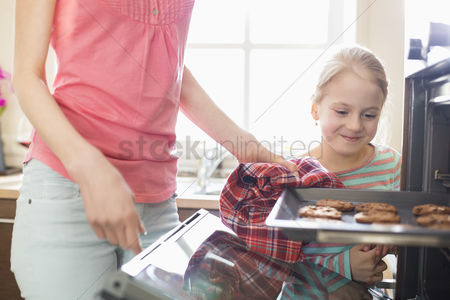 Pre teen : Smiling looking at mother removing cookie tray from oven at home