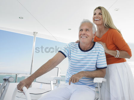 Transportation : Smiling middle-aged couple at helm of yacht
