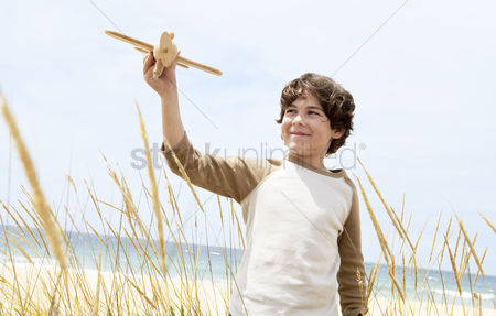 Pre teen : Smiling pre-teen boy standing arms raised on beach among plants flying toy airplane
