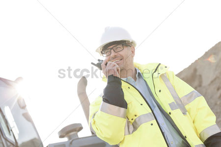 Supervisor : Smiling supervisor using walkie-talkie at construction site against clear sky