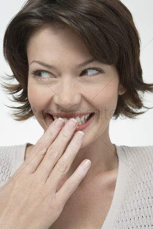 Shyness : Smiling woman covering mouth with hand looking away close-up