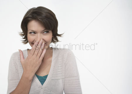 Shyness : Smiling woman covering mouth with hand