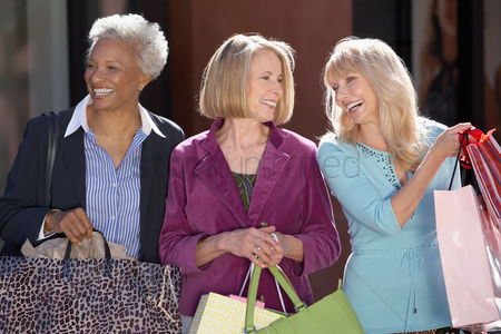 Friends : Smiling women walking outside carrying bags on shopping trip