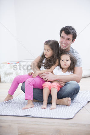 Sitting on lap : Smiling young man with daughters sitting in his lap at home
