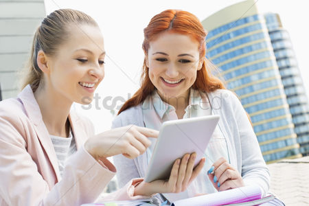 College : Smiling young university students using digital tablet against building
