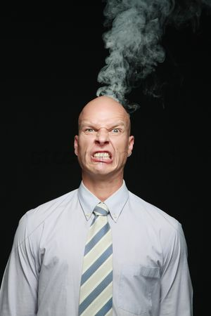 Frowning : Smoke coming out of businessman s head