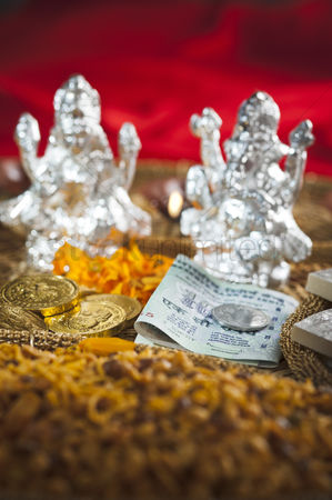 God : Snacks and money in front of idols of lakshmi and ganesh during diwali festival