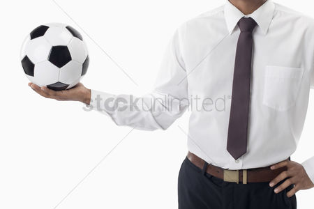 Masculinity : Soccer manager holding a ball with one hand