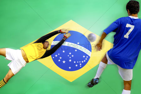 Pitch : Soccer player scoring goal in front of brazilian flag