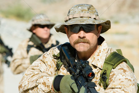 Alert : Soldier carrying rifle outdoors