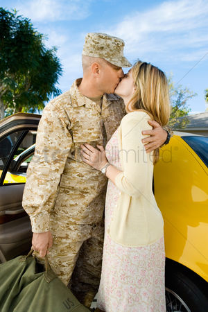 Kissing : Soldier kissing wife by car