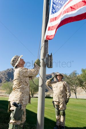 Respect : Soldiers raising united states flag outdoors