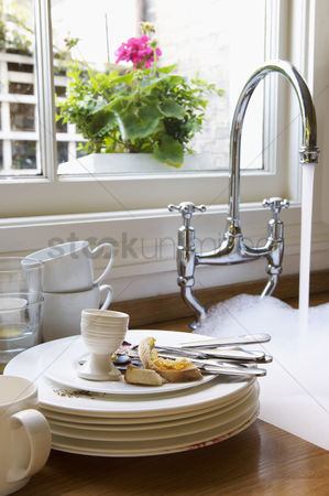 Interior : Stack of dirty dishes and silverware by sink with running water below window with flower