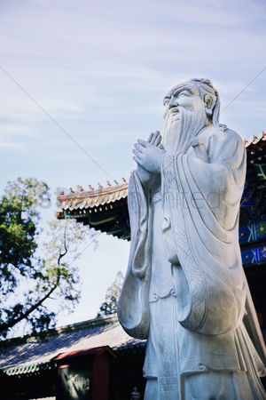 Sculpture : Stone statue of confucius  traditional pagoda in the background