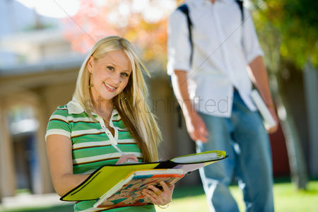 High school : Student writing in notebook outdoors  portrait