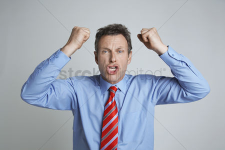 Pressure : Studio shot of businessman shaking his fists