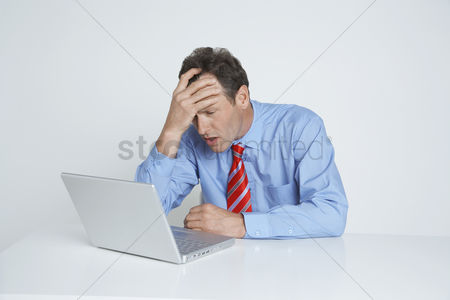 Pressure : Studio shot of businessman with head in hands using laptop