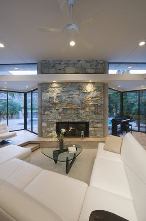 Furniture : Sunken seating area and exposed stone fireplace of palm springs home
