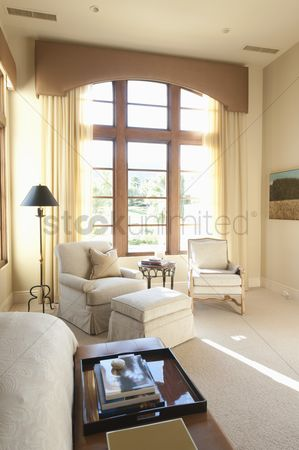 High ceiling : Sunlit floor to ceiling windows in cream living room interior