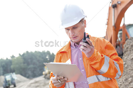 Supervisor : Supervisor reading clipboard while using walkie-talkie at construction site