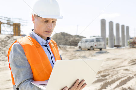 Supervisor : Supervisor using laptop at construction site on sunny day