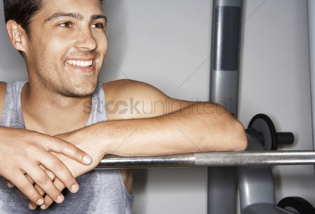 Club : Sweaty man resting on barbell after workout