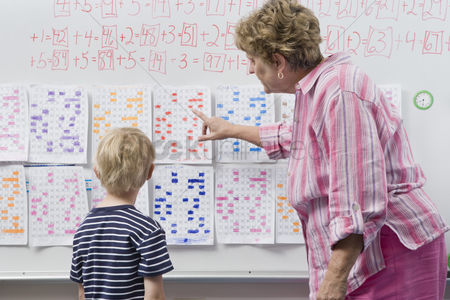 School children : Teacher explaining calendar to little boy
