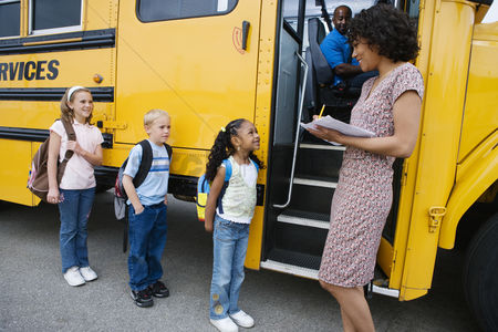 School children : Teacher loading elementary students on school bus