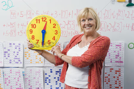 Instruction : Teacher showing class a clock