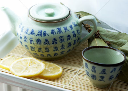 Refreshment : Teapot with tea cup and sliced lemons on a tray