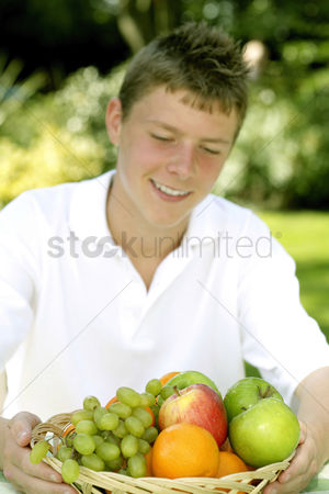 Green grapes : Teenage boy holding a basket of fruits
