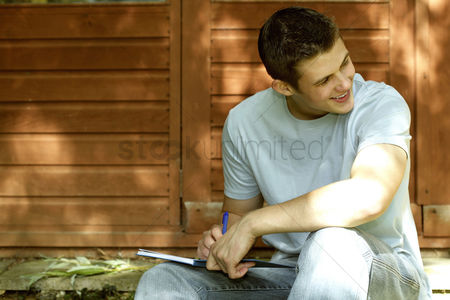 Outdoor : Teenage boy smiling writing journal