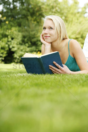 Lying forward : Teenage girl lying forward on the field holding book