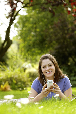 Lying forward : Teenage girl lying forward on the field listening to music on a portable mp3 player