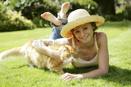 Lying forward : Teenage girl lying forward on the field with her cat