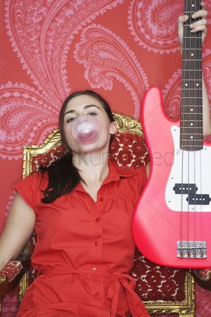 Blowing : Teenage girl sitting blowing bubble holding up guitar