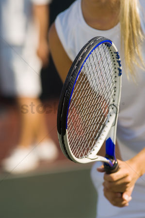 Match : Tennis player holding racket waiting for doubles partner to serve close-up mid section