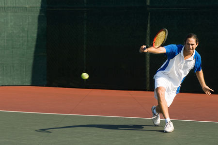 Match : Tennis player squatting on tennis court hitting backhand