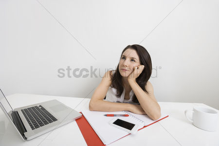 Cell phone : Thoughtful businesswoman with laptop and binder at desk in office