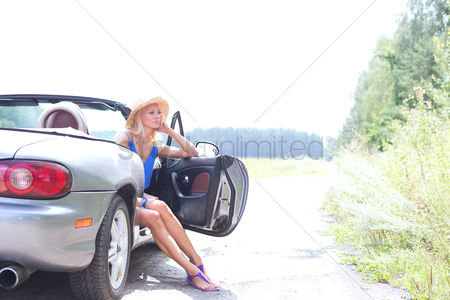On the road : Thoughtful woman sitting in convertible on country road against clear sky