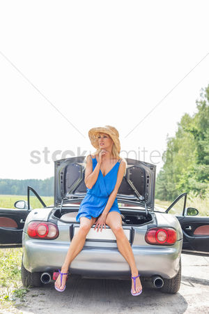 On the road : Thoughtful woman sitting on convertible trunk against clear sky