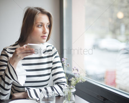 Czech republic : Thoughtful young woman looking out from window while drinking coffee in cafe