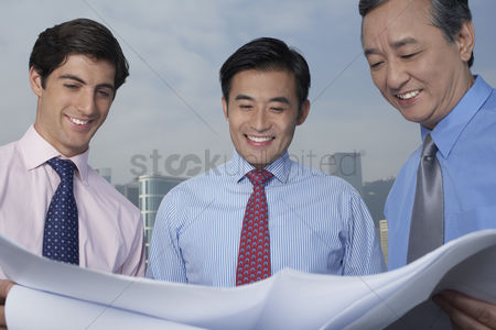 Moody : Three business men holding and looking at blueprints smiling