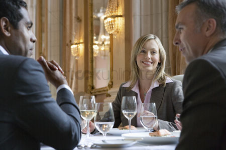 Business suit : Three business people sitting at restaurant table talking