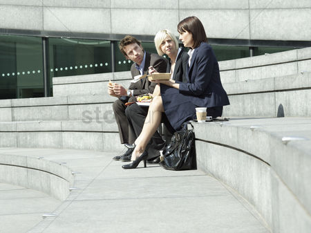 Stairs : Three business people sitting on stairs outdoors talking side view