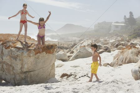 Day off : Three children playing on rocky beach