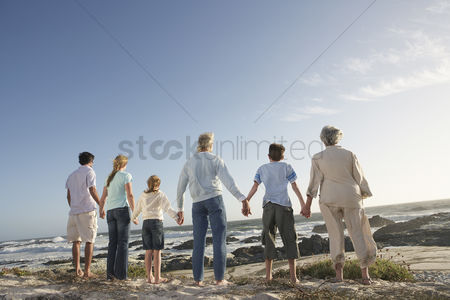 Daughter : Three generation family holding hands on seashore back view