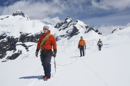Rope : Three hikers joined by safety line in snowy mountains