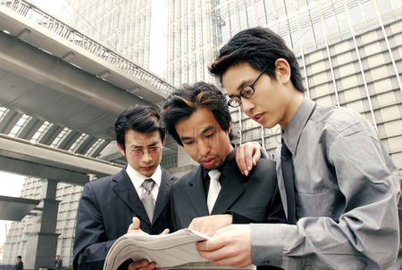 Bespectacled : Three men in formal wear sharing a newspaper