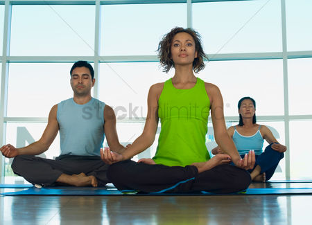 Young woman : Three people doing yoga indoors